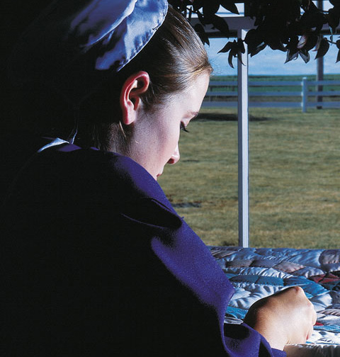 Amish woman working on a quilt.